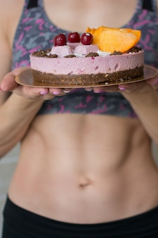 Healthy raw cake in the girl's hands with a sports body.
