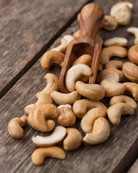 Healthy raw cashew nuts and small wooden spoon