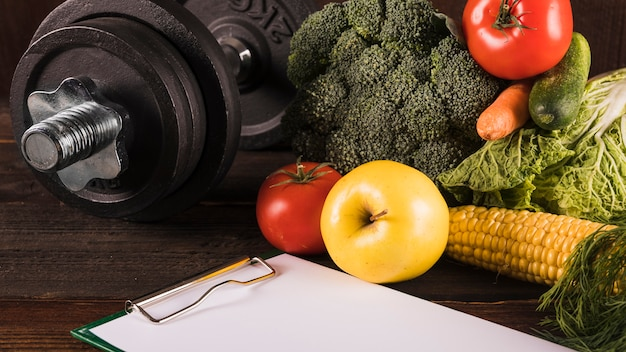 Healthy raw food and dumbbell on wooden surface