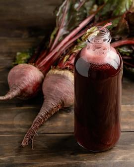 Здоровый красный напиток в расположении стеклянных бутылок