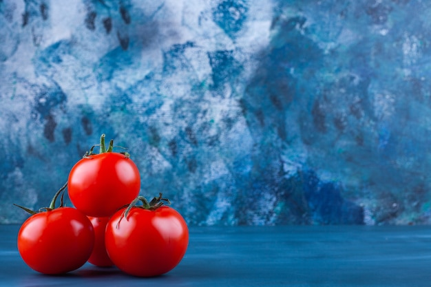 Healthy red fresh tomatoes placed on blue surface