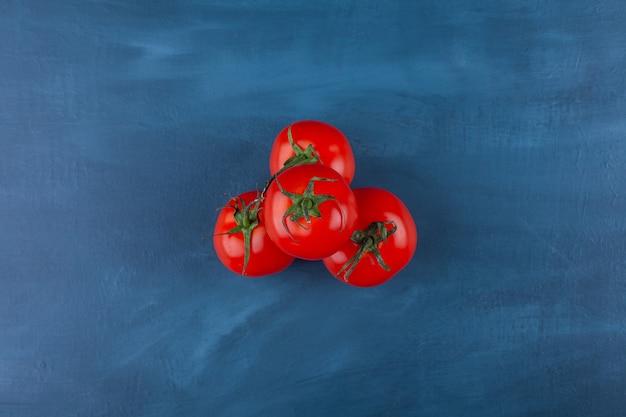 건강 한 빨간 신선한 토마토는 파란색 표면에 배치.