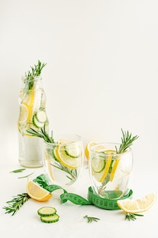 Healthy refreshing detox water with rosemary,lemon and cucumber on white background