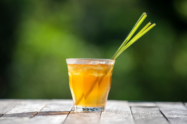Healthy, refreshing drink of cinnamon and stalks of lemongrass on a wooden table in a tropical garden