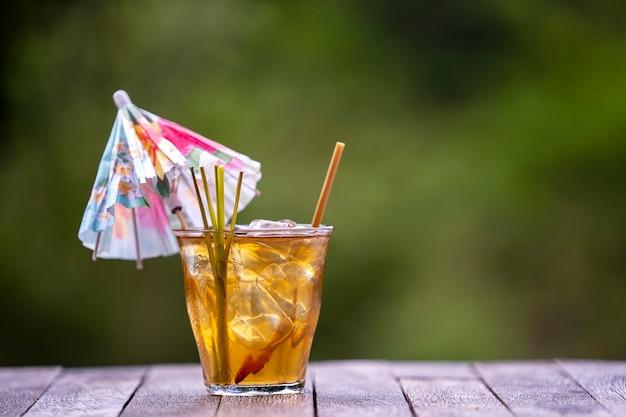 Здоровый, освежающий напиток из корицы и стеблей имбиря на деревянном столе на фоне зеленого тропического сада, крупным планом, копией пространства. малайзия