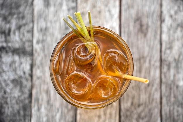 木製のテーブル、上面図、クローズアップにシナモンとレモングラスの茎の健康的でさわやかな飲み物