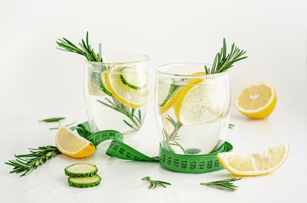 Healthy refreshing infused water with rosemary,lemon and cucumber on white background
