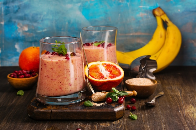 Healthy refreshing pink smoothie with apple, red oranges, cowberry and bran