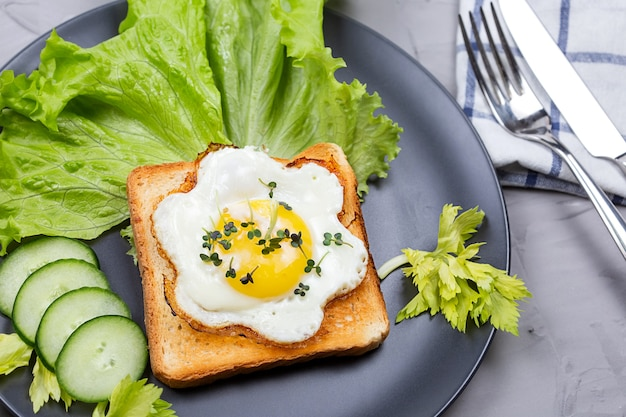 Healthy restaurant breakfast with fry pan eggs with salad on white background top view