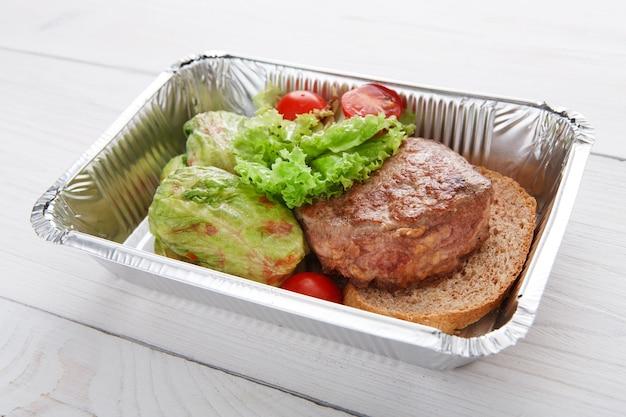 ホイルボックスで健康的なレストランの食品配達。クリエイティブな料理。茶色のパンに子牛のステーキを添えたグリーン煮込みロールキャベツ。牛肉と野菜のチェリートマト添え。レストランの料理はクローズアップを奪います。