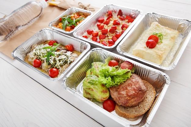 ホイルボックスで健康的なレストランの食品配達。茶色のパンやその他の料理に子牛のステーキを添えたグリーン煮込みロールキャベツ。牛肉と野菜のチェリートマト添え。食事はクローズアップを奪います。