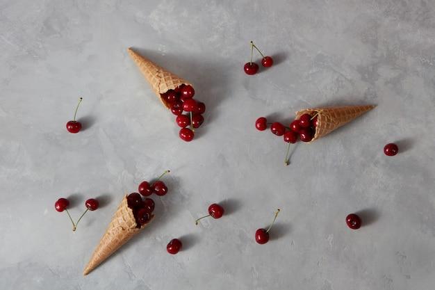 Здоровые спелые красные фрукты вишня и вафельные чашки для домашнего мороженого на сером каменном фоне с местом для текста. летом органическое питание.