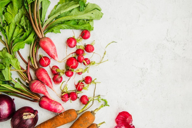 Healthy root vegetables on marble backdrop
