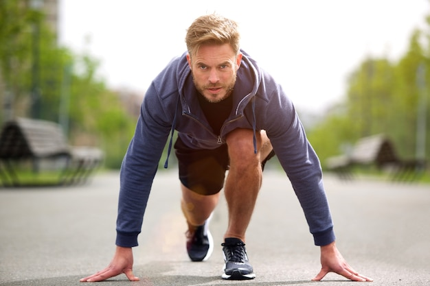 Healthy runner in starting position outside