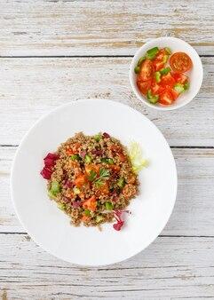Здоровый деревенский салат из киноа с овощами на белом деревянном столе