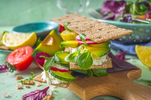 Healthy rye bread sandwiches with crispy bread, cream cheese and fresh spring vegetables