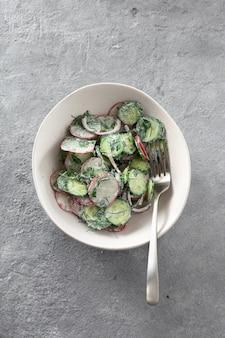 Healthy salad bowl radish cucumber yogurt top view
