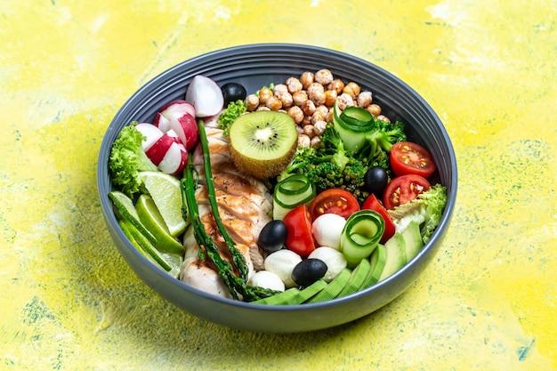 黄色の背景にアボカド、アスパラガス、ひよこ豆、ブロッコリー、大根、鶏肉、きゅうり、トマト、オリーブ、モッツァレラチーズのヘルシーなサラダボウル。上面図。食品と健康