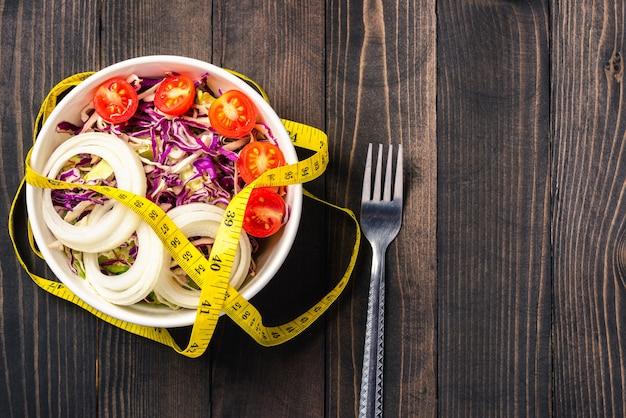 Здоровый салат с помидорами, свежими овощами в блюде и измерительной лентой
