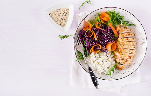 Healthy salad. buddha bowl dish with chicken fillet, rice,  red cabbage, carrot, fresh lettuce salad and sesame