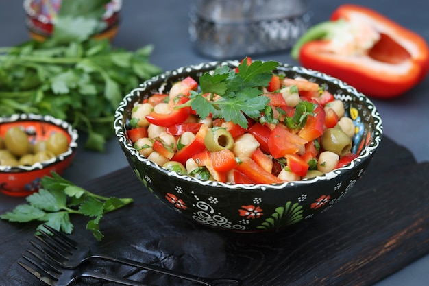 Healthy salad of chickpea, green olives, pepper and parsley located on wooden board on black