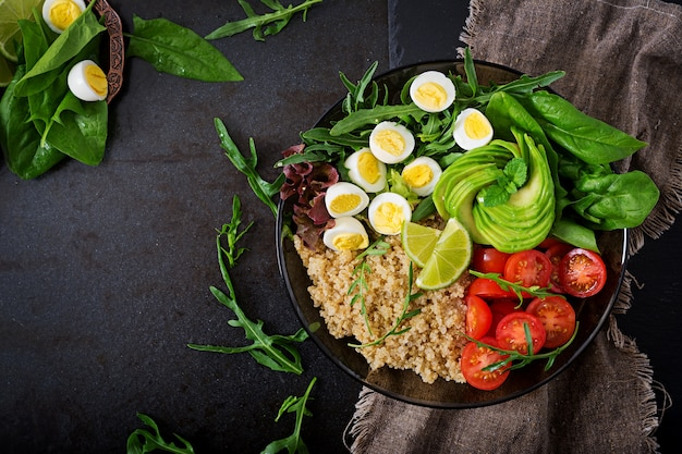 Healthy salad of fresh vegetables - tomatoes, avocado, arugula, egg, spinach and quinoa