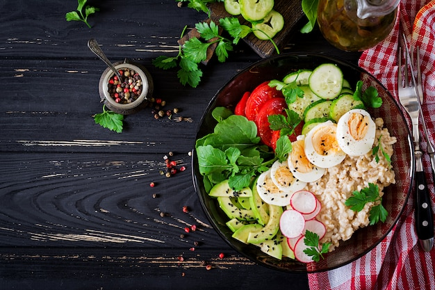 Healthy salad of fresh vegetables - tomatoes, avocado, cucumber, radish, egg, arugula and oatmeal on bowl. diet food. flat lay. top view