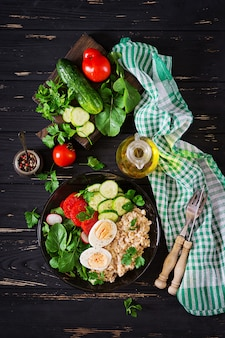 Healthy salad of fresh vegetables - tomatoes, cucumber, radish, egg, arugula and oatmeal on bowl. diet food. flat lay. top view