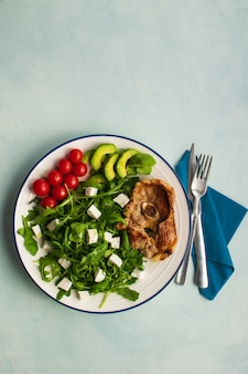 Healthy salad of fresh vegetables with cubes goat cheese and lamb chop in a plate.