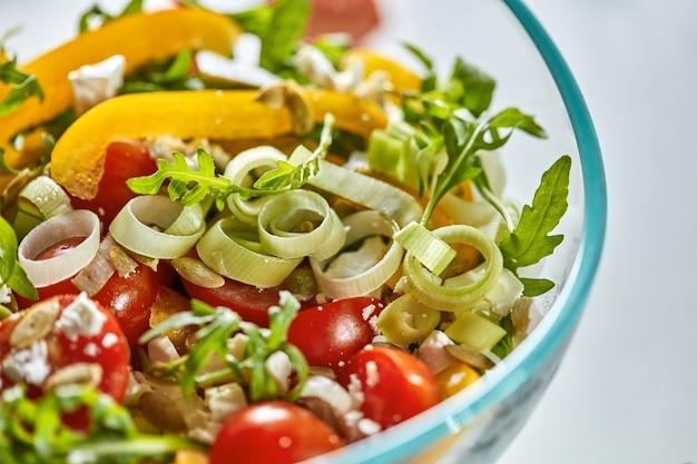 Полезный салат из перца, рукколы, лука-порея, помидора и сыра в прозрачной миске