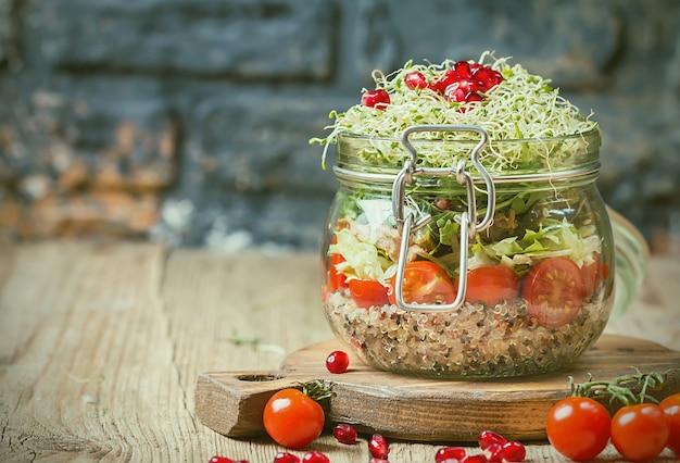 キノア野菜と緑の健康食品またはダイエットの概念とガラスの瓶の健康的なサラダ