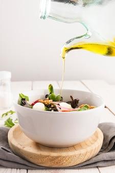 Здоровый салат в белой миске с оливковым маслом