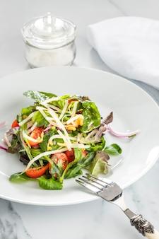 Здоровый салат в составе белой тарелки
