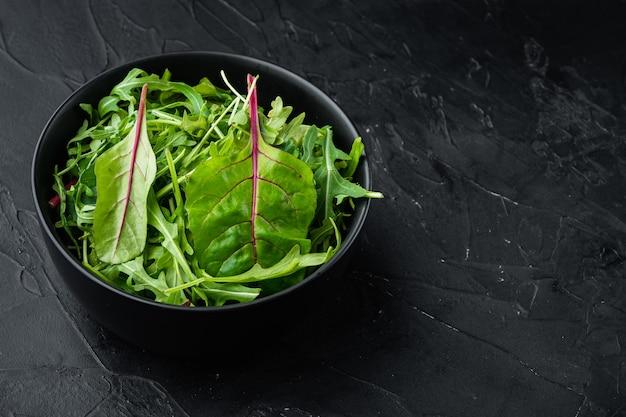 건강한 샐러드, 잎 믹스 샐러드 arugula, chard 세트, 검은 돌 배경, 텍스트 복사 공간