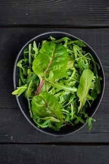 Здоровый салат, салат из микса листьев руккола, мангольд, на фоне черного деревянного стола, плоская планировка, вид сверху