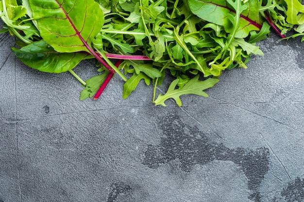 Здоровый салат, салат из микса листьев, руккола, мангольд, на сером каменном фоне, плоский вид сверху, с копией пространства для текста