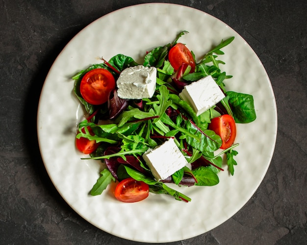 Healthy salad leaves in a white plate and cheese ( juicy snack). food background