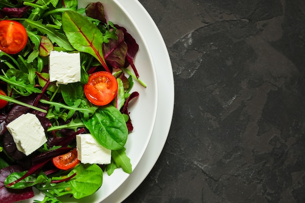 Healthy salad leaves in a white plate and cheese (mix micro greens). food background