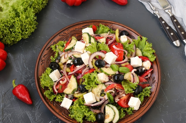 Healthy salad of lettuce, tomato, red onion, pepper, soft cheese, olives, basil, cucumbers, with olive oil and lemon juice. greek salad