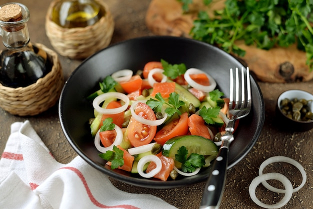Полезный салат из помидоров черри, огурцов, сельдерея, лука, каперсов и петрушки с малосольным лососем.