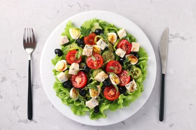 チェリートマト、きゅうり、ピーマン、ブラックオリーブのヘルシーサラダ、オリーブオイル、ウズラの卵、ゴルゴンゾラチーズを明るい面に、上からの眺め