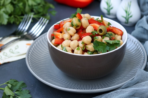 Полезный салат из нута, зеленых оливок, перца и петрушки, расположен на темной поверхности, фото горизонтально