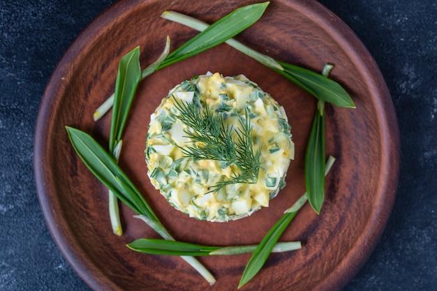 녹색 야생 부추, 수란, 사워 크림의 건강 샐러드를 닫습니다. 삶은 계란과 야생 마늘 샐러드