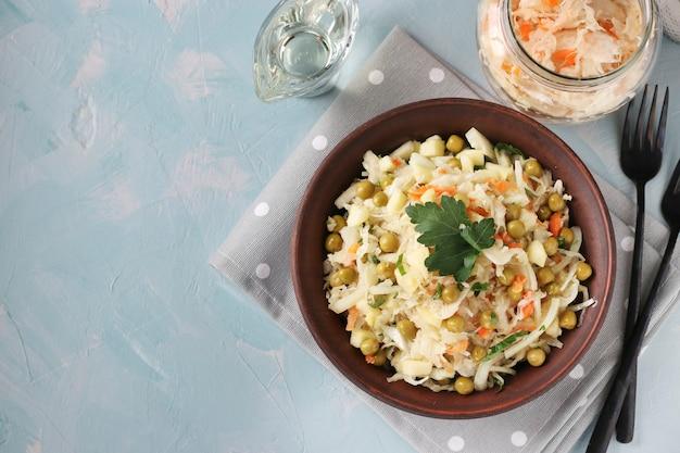 ザワークラウト、缶詰のエンドウ豆、にんじんのヘルシーサラダを水色の表面にボウルに入れて、上面図、コピースペース
