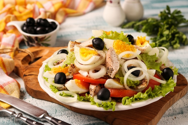 Healthy salad of organic lettuce with chicken, tomatoes, eggs, black olives and white onions