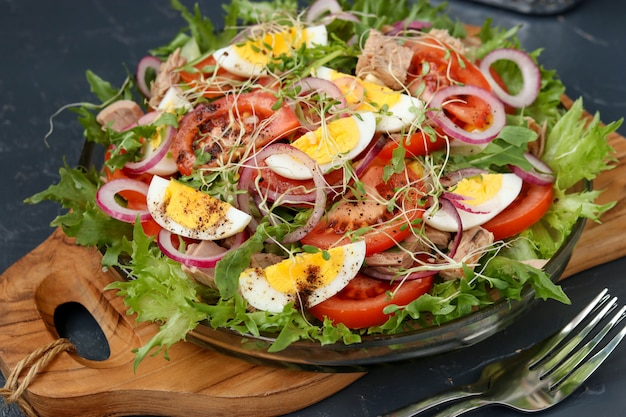 Healthy salad of organic salad with canned tuna, tomatoes, chicken eggs and red onion.