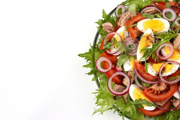 Healthy salad of organic salad with canned tuna, tomatoes, eggs, arugula, red onion and microgreen in a plate on a white background
