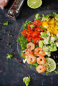 Healthy salad plate. fresh seafood recipe. grilled shrimps and fresh vegetable salad - avocado, tomato, black beans, red cabbage and paprika. grilled prawns. healthy food. flat lay.