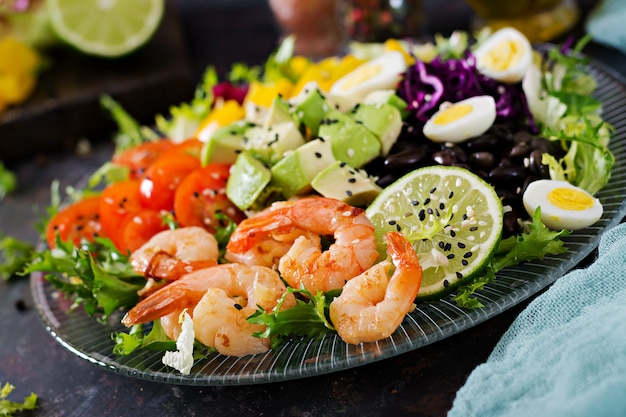 Healthy salad plate. fresh seafood recipe. grilled shrimps and fresh vegetable salad - avocado, tomato, black beans, red cabbage and paprika. grilled prawns. healthy food.