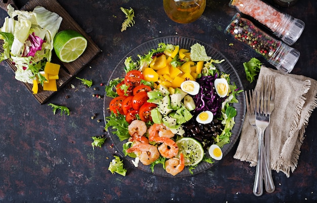 Healthy salad plate. fresh seafood recipe. grilled shrimps and fresh vegetable salad - avocado, tomato, black beans, red cabbage and paprika. grilled prawns.
